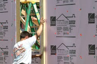 Worker installs insulation during home construction